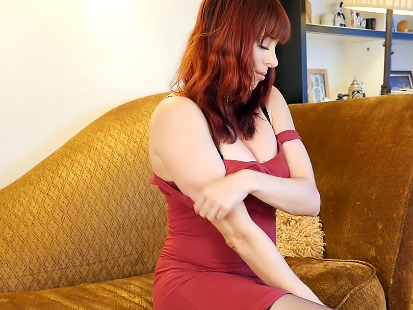 Mature redhead Odile shoves dildo inside her wet pussy.