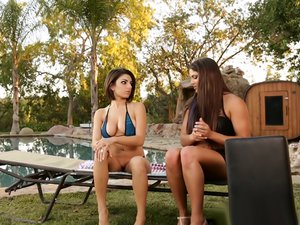 Busty bombshells have lesbian action by the poolside.